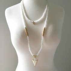 """This double wrap necklace has semi-precious White Jade and Magnesite beads along with gold accents and anchored with a 24k gold edged carved bone arrowhead. Necklace measures approximately 21"""" includi"""