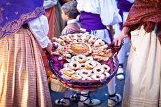 Mulheres segurando uma cesta de pães na festa do Pilar em Zaragoza (Saragoça), Espanha  Zaragoza é uma cidade universitária muito importante e é o primeiro centro mariano espanhol que venera a Virgem do Pilar.  As festas do Pilar são na semana de 12 de outubro, e nesse dia pela manhã há uma oferenda de flores para a Virgem.  No dia 13 se inicia uma procissão do Rosário de Cristal, à luz de 350 velas levadas por carroças.   Se celebram também os desfiles de Gigantes e Cabeçudos, concursos de…