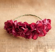 Este bonito y llamativo complemento de flores de tela está realizado únicamente con pétalos de hortensias de distintos tamaños en un tono vino rosado. Trenzado en la parte posterior, para dar un toque muy natural al resultado final.