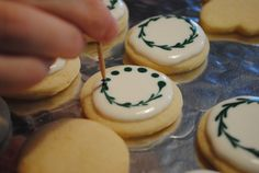 Sweet, tender little sugar cookie circles are first topped with a generous, glossy dollop of simple icing.  Before the icing can dry, little dots of green food coloring are applied around the edges with a toothpick.  Last but not least, drag the toothpick through the icing dots to connect them in a swirly wreath-like pattern.  So pretty, so festive!