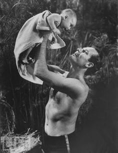 """Charlton Heston holds up his son Fraser on the set of """"The Ten Commandments"""" (Fraser would play baby Moses in the movie) (1956)"""