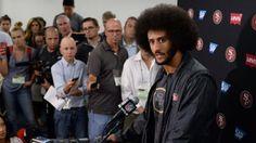 San Francisco 49ers quarterback Colin Kaepernick (right) talks to media after…