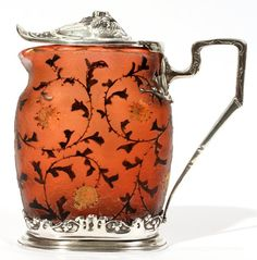 Carved cameo glass and silver-mounted syrup pitcher by Daum, ca.1900. Glass is a warm puce-like hue (dark red or purple-brown) with gilt thistle and coloured vine motif, mounted with ornate silver hinged cover, handle and foot, 4 1/2 x 4 1/2""