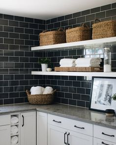 Don't be afraid to incorporate deeper shades into your design! Give classic white subway tile a refresh by using a darker color. @timbertrailshomes paired it with white cabinets and open shelving to ground the design. ​Photo by @stofferphotographyinteriors.  #thetileshop #subwaytile #laundryroom