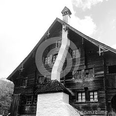 A beautiful black and white image of an old traditional Swiss home built of wood with an incredible curved chimney. This is in the Alps at the Ballenberg Museum.