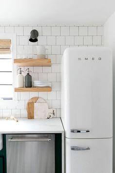 kitchen   dark green cabinets, white smeg fridge, open wood shelving + full-wall tile