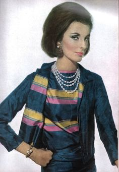 Mrs. Patrick Guinness, circa 1962, in a silk Chanel suit of midnight blue banded by clover pink and yellow stripes. The 'new' Chanel suit had a tighter silhouette, and had a collar and lapels. No mention of the pearls' provenance but her bracelet was also Chanel.  Mrs. Guinness was always a fashion plate. Here she was in 1959, when she was still a blonde and every bit as chic, sporting a black Dior dress and lace mantilla. Photo above from Vogue, April 1962.