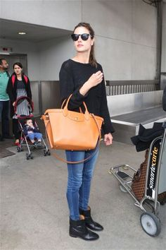 50 Airport Outfits to try: Alessandra Ambrosio wearing a cozy black sweater, skinny jeans, black ankle boots + oversized camel-colored leather tote