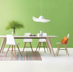 Weisse Esszimmermöbel mit einer grünen Wand und einem farbigen Teppich sind frisch und modern.