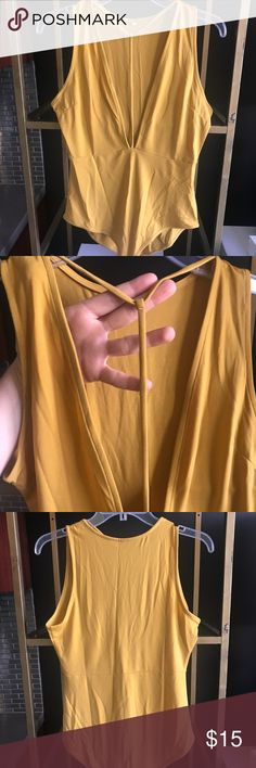 Cute sexy saffron deep v strapped bodysuit This is for the super confident lady that knows she looks great. In this pretty mustard/ saffron color, you also avoid looking too dominatrix about it ;) Extra deep v is set off by t strap at neck that runs down the center of the chest. Cut hugs your curves to perfection, top is unlined. Two snaps keep all in place. Rayon, spandex. New, never worn, without tags. Tops Camisoles