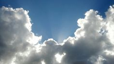 Sunbeams against a dark blue sky and backlit clouds provide a gorgeous view.