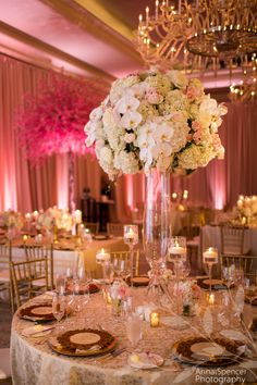 Wedding Reception in the Astor Ballroom at the St. Regis in Atlanta. Tall white orchid and pink floral arrangement with gold linens in a pink ballroom