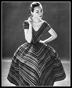 Model Sandy Brown in quilted striped dress, full skirt, v-neckline and short sleeves by Anne Fogarty, Vogue, February 1, 1952