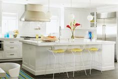 Beach cottage kitchen features three white glass globe pendants illuminating a white center island topped with thick white marble counter fitted with sink and pull-out faucet lined with white Bertoia Barstools accented with yellow seat cushions.