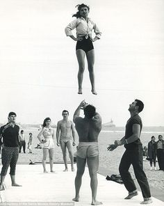 1957, Muscle Beach, California:  a girl is tossed in the air in a show of skill and strength