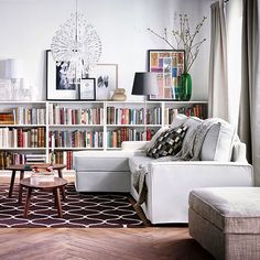 Low bookshelves provide interest, colour and space, with understated neutral furnishings