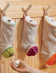 Hang these ingenious harvest storage bags anywhere to conveniently store and dispense vegetable crops like onions, garlic and potatoes. They're made from a cotton and linen fabric that allows air to circulate but blocks out light to prevent sprouting. There are drawstrings with toggles at the top and bottom for easy filling and dispensing, and a hanging loop on back.