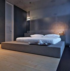 A platform bed  raised to a comfortable height with tailored, crisp linens; and how practical it would be with slide out drawers.