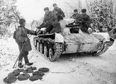 A light T-60 Russian tank and riders meet with a sapper and nine mines he has discovered with his VIM-210 mine detector. Winter 1942.