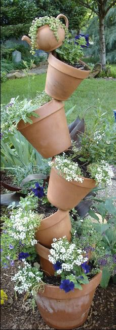 Tipsy Pots : easy to make, just ram a rod of rebar iron into the bottom pot, fill with dirt, and start layering pots through the drain hole, tilting each to one side or the other. Nice filled with herbs or flowers.