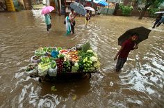 An Indian vegetable vendor stands with his fully-loaded stall on a flooded street in Mumbai, India.