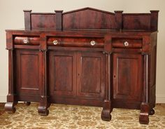 American Greek Revival. Sideboard. Curved drawer front, mahogany curved arch on storage door, engaged tuscan column, emphasis on straight lines and large scale, animal paw feet.