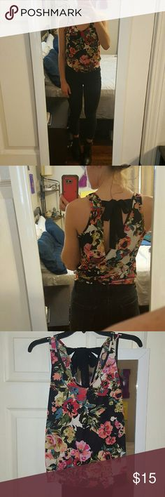 Floral Tank 100% polyester. Looser fit, fitted at waist band. Open back with black strings to tie. Lilly Star Tops Blouses