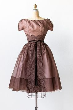 1950s brown organza lace party dress. This dress features short sleeves, a high rounded neckline, and lace detail under the bust and down the front center skirt. The skirt is full and can be worn with crinoline underneath for extra volume. There is a zipper closure down the back center.