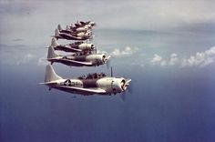 A flight of Douglas SBD Dauntless scout bombers over the Caribbean, 1944. Good view of the two-tone gray and white scheme widely used in th…