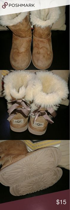 Girls UGG Boots Size 2 Bows These boots are in nice preowned condition. Accept for water stains these shoes are in nice shape. Insides are fluffy. No holes or rips. UGG Shoes