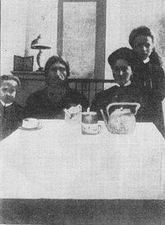 Rasputin sits at a table with Alexandra, Anastasia and Olga