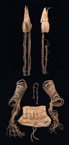 "Africa | Diverse jewellery and ornaments worn by the Himba women of Namibia | 1) bodice-like garment ""omutombe"", consisting of discs made of ostrich eggs, which are threaded on cord material and arranged in rows, strengthened by vertical wooden sticks, wrapped up with leather straps, 2) two leg ornaments; iron beads, threaded on leather straps, 3) two head crests: bonnet-shaped, made of brown leather, embroidered with iron beads"