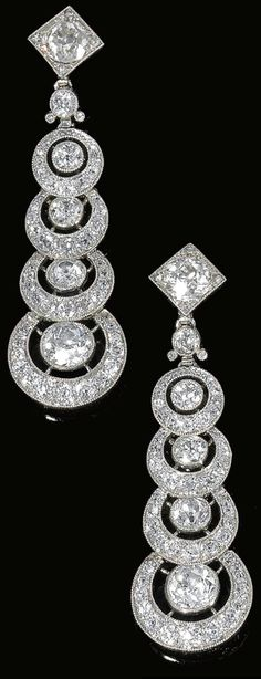 Art Deco diamond earclips by Cartier, circa 1910. Each designed as a graduated series of open work circular motifs, millegrain-set with circular-, single-cut, and rose diamonds, signed Cartier, later modifications, screw back fittings. Via Sotheby's.