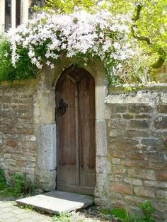 stone wall, garden gate, white climber - this picture has a feeling of such peace behind those walls
