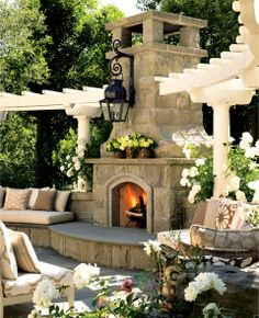 Green/white landscaping creates a fresh and clean outdoor area  Outdoor porch, fireplace with lantern is an interesting idea, extra seating creates an inviting area