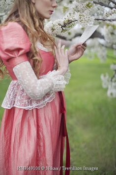 Trevillion Images - historical-woman-reading-letter-by-tree