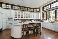 White cabinet kitchen with oval island with breakfast bar and wood flooring.