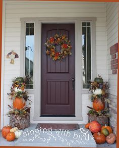 Front porch with wreath and pumpkin topiaries.