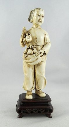 """Chinese Cultural Revolution Hand Carved Ivory Figure. Young child holding a basket of fruit. Measures - 6 1/4"""" high x 2 1/4"""" wide."""