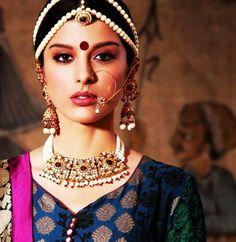 Indian bride wearing bridal lehenga and pearl jewelry. #IndianBridalHairstyle #IndianBridalMakeup #IndianBridalFashion