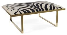 Add an element of exotic glamour to the room with this brass coffee table, upholstered in zebra-print hair-on hide. Handcrafted in the USA.Taylor Burke Home is a boutique furniture company proudly...