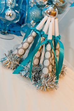 """Great party horns!  from the site: """"To create these, I simply recovered Dollar Tree noisemakers in silver polka dot glitter scrapbook paper and finished it with a length of teal ribbon and silver garland."""""""