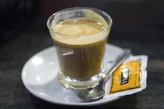 """Café Cortado. A cortado is an espresso (also known as """"Pingo"""" or """"Garoto"""") """"cut"""" (from the Spanish and Portuguese cortar) with a small amount of warm milk to reduce the acidity. The ratio of milk to coffee is between 1:1 – 1:2, and the milk is added after the espresso."""