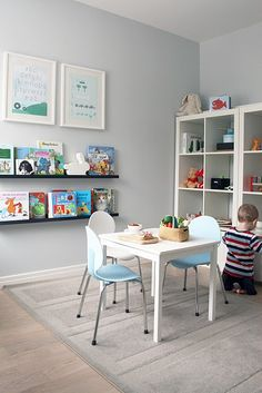play and reading space. low long book ledges with framed art above.