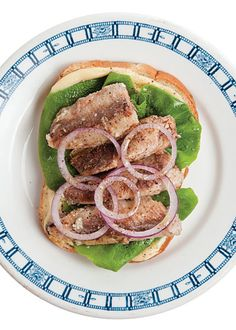 Saveur Sardine sandich (serves 2) - 3 tbsp. Dijon mustard2 slices rye bread, toasted2 large leaves bibb lettuce1 4-oz. can sardines in oil, drained, plus 2 tsp. reserved oil½ small yellow onion, thinly sliced crosswiseKosher salt and freshly ground black pepper, to taste