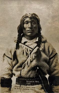 Photograph, studio portrait of Beaver Tail, an Assiniboine man; wearing a wool coat over a garment, and waist belt with bullets and a knife in a sheath.     by: Geraldine Moodie