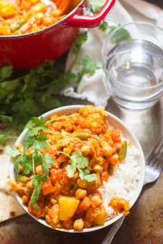 Veggies and chickpeas are simmered in a spiced tomato sauce and served atop basmati rice to make this super easy and delicious mixed vegetable curry.