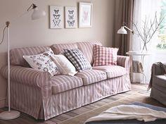 Un salón con un sofá de tres plazas con una funda beige/roja lleno de cojines
