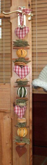 A long herbal decoration which could be hung on a dresser, by the fireplace, on a door etc. It features three homespun fabric hearts stuffed with polyester, whole split oranges, apple slices, orange slices, bay leaves, cinnamon sticks and nutmegs, with a cinnamon dough heart at the bottom and matching fabric tie at the top. Scented with cinnamon fragrance oil.