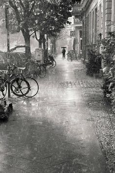 The rain, the perspective leading up to the figure with the umbrella, the bikes, black and white photography Walking In The Rain, Singing In The Rain, Rain Photography, Street Photography, Rainy Day Photography, Vintage Photography, Black White Photos, Black And White Photography, Black And White City